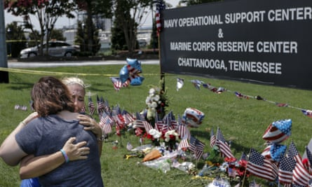 People embrace in front of a makeshift memorial at the Navy Operational Support Center and Marine Corps Reserve Center for the victims of the 16 July shootings in Chattanooga, Tennessee.