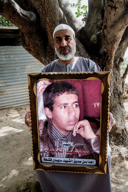 Shuaib Hussein Behabsa with a poster of his 17-year-old son, Mohammad, a pupil at Doha school in Rafah, who was killed during an air and artillery strike on his home.