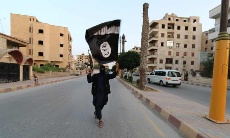 A fighter waves an ISIS or ISIL flag in Raqqa, Syria.