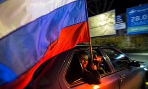 A man holding a Russian flag looks out of the car window during the celebrations for the first anniversary of the Crimean treaty-signing.