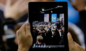 President Barack Obama is seen on a video tablet as he shakes hands after speaking at a campaign event