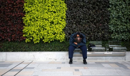 A man takes a nap on a bench in Tokyo.