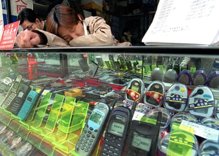 A vendor takes a nap on his counter in Shanghai. 'China has a healthy napping culture'.