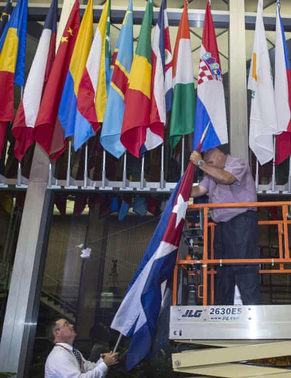 Workers at the US State Department add the Cuban flag at to the display inside the main entrance early on Monday morning.
