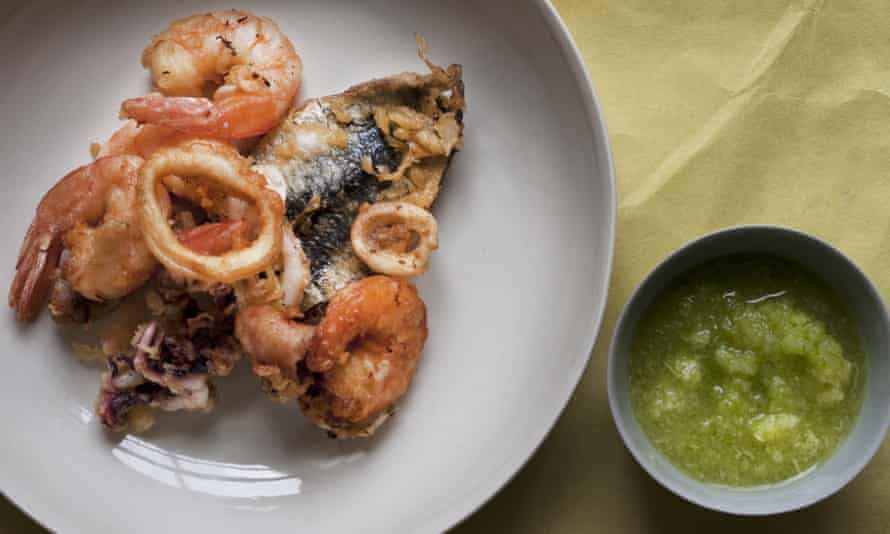 Deep-fried seafood on a plate next to a small bowl of sour apple and ginger sauce