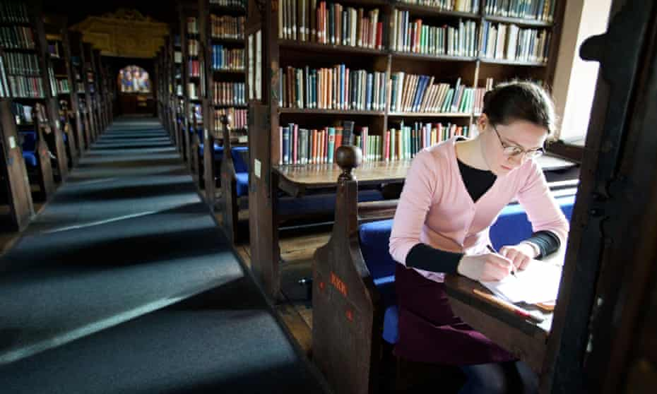 Woman sits at table in library writing notes