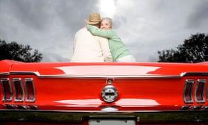 older couple sitting on sports car