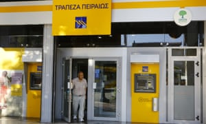 A customer leaves a Piraeus Bank branch in Athens, Greece.