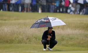 Adam Scott shelters from the rain, he is slipping out of contention.