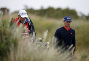 Adam Scott walks with his caddie, he dropped five shots in the final five.