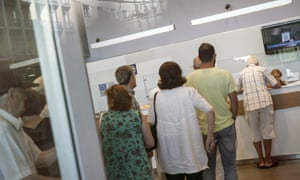People stand in line inside a bank in Athens today.
