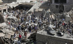 People gather on the rubble of shops destroyed by a Saudi-led airstrike at a market in Sanaa, Yemen,  July 20, 2015.