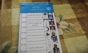 A stack of ballots shows candidates for president including the country's longtime ruler Omar al-Bashir, top, inside a polling station on the first day of Sudan's presidential and legislative elections.