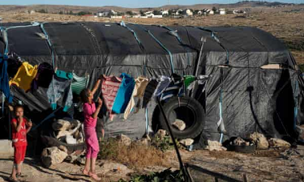 One of the temporary structures that is home to the villagers of Khirbet Susiya with the Israeli settlement of Susiya in the background. Banned from building by the Israeli authorities, the 80 or so shelters provide homes for several hundred Palestinians in the south of the West Bank. Unlike the Israeli settlement Khirbet Susiya is not connected to running water.