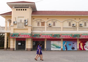 Two employees of the karaoke bar walk past empty and locked up shops on their way to work in Spanish Town
