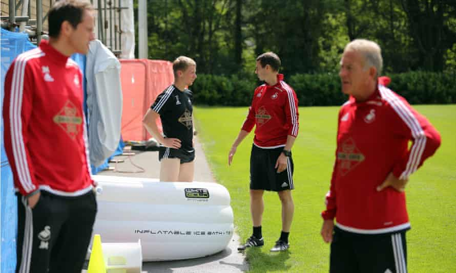 The left-back Stephen Kingsley stands in an inflatable ice bath at Swansea's training ground.