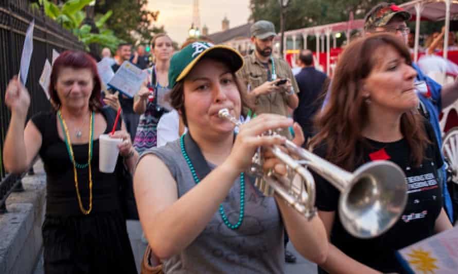 Karissa McKelvey plays the trumpet as Strike Debt members march through New Orleans
