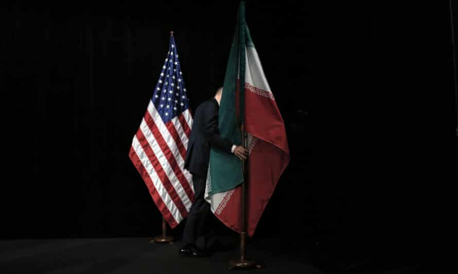 A member of staff removes the Iranian flag from the stage after the nuclear talks in Vienna. Iran and six major world powers reached a nuclear deal this week capping more than a decade of on-off negotiations with an agreement that could potentially transform the Middle East, and which Israel called an 'historic surrender'.