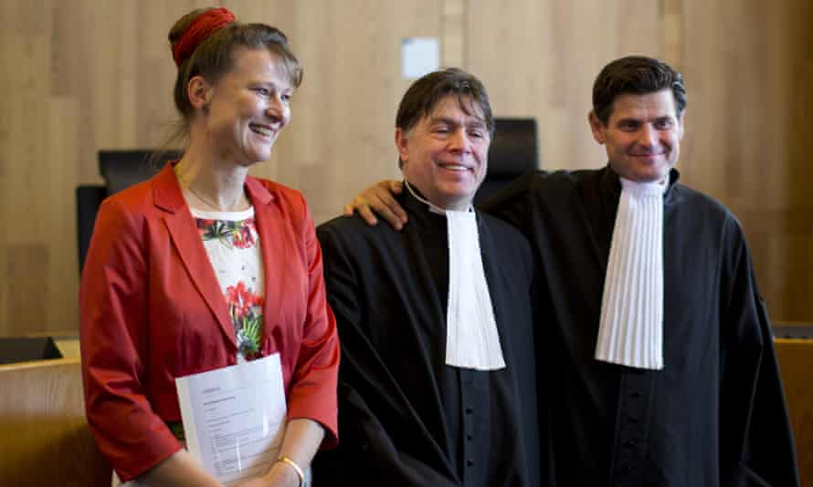 Urgenda Foundation director Marjan Minnesma, left, and lawyers Koos van der Berg, center, and Roger Cox, right, pose for pictures after a Dutch court ordered the government to cut the country's greenhouse gas emissions by at least 25 percent by 2020 in a groundbreaking climate case that activists hope will set a worldwide precedent in The Hague, Netherlands, Wednesday, June 24, 2015. The Hague District Court made the ruling Wednesday in a case brought by a sustainability organization on behalf of some 900 citizens, claiming that the the government has a duty of care to protect its citizens against looming dangers. (AP Photo/Peter Dejong)