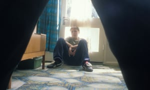 young boy sitting by door being threatened by adult man