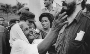 Fidel Castro (R) enduring what appears to be a beard tickling from elderly peasant woman while visiting Oriente province.