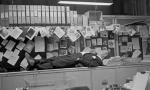 An office worker taking a nap on top of the filing cabinet