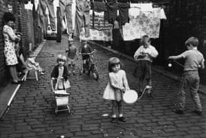 The cobbled lane between terraced houses in Chorlton-on-Medlock becomes both playground and laundry, 1966.