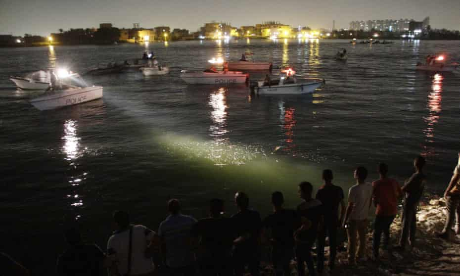 Egyptian police and rescue boats at the scene of deadly collision between a cargo boat and a ferry.