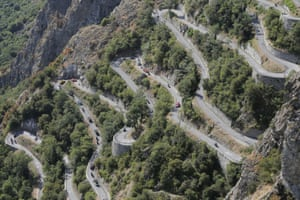 Riders, team cars and press motorcycles climb the Lacets de Montvernier during the stage.