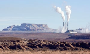 Bare rock and earth in foreground, red/brown, rock outcrops at the horizon, and to the right three tall chimneys and industrial buildings billowing smoke.