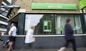 Job seekers walk past a job centre
