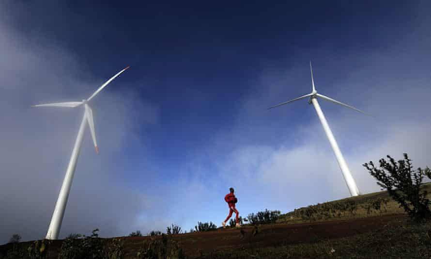 A man running past wind turbines in the early morning mist in the Ngong hills, some 25 kms south-west of Nairobi.