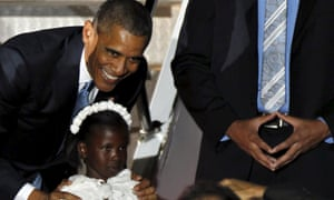 Barack Obama poses for a photo with a girl after receiving flowers from her upon arrival.