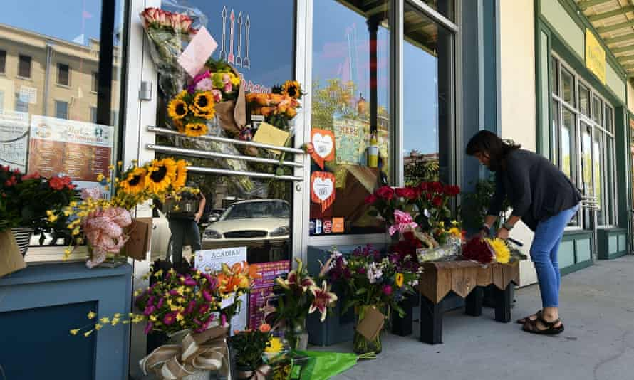 A local resident leaves flowers at a makeshift memorial outside of a store owned by one of the victims, Jillian Johnson, on Friday in Lafayette, Louisiana. shooting theater