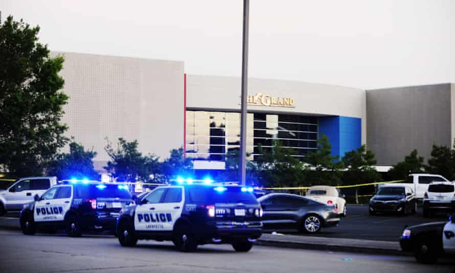 Law enforcement and other emergency personnel respond to the scene of the shooting at the Grand 16 movie theater.