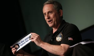 Alan Stern, principal investigator of NASA's New Horizons mission team, holds up a bumper sticker  at Nasa headquarters on Friday.