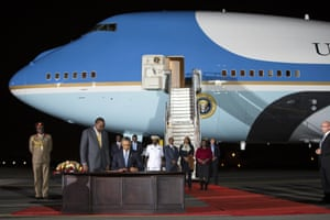Kenyan president, Uhuru Kenyatta, watches as Obama signs a guest book after arriving at Kenyatta airport.