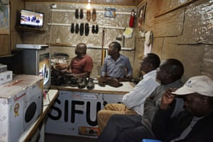 Men watch the arrival of Obama on television at a local bar in Kibera, Nairobi.