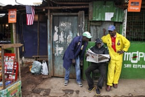 People read a newspaper announcing Obama's official four-day east Africa state visit.