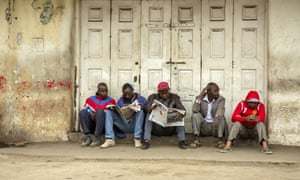 Men read newspapers on the side of the road in Nairobi.