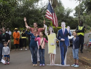 People wave an American flag alongside a cutout of the Duke and Duchess of Cambridge as Obama's motorcade arrives.