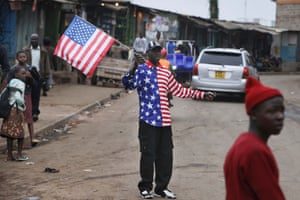 A man waves a US flag in Kibera.