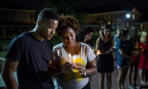 Students pray during a candlelight vigil for the Grand 16 theater shooting victims at the University of Louisiana at Lafayette.