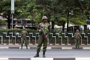 General Service Unit officers stand guard by Kenyatta avenue in Nairobi as crowds gather to watch the passing of Obama's motorcade.