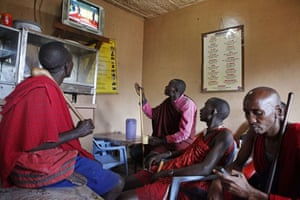 Maasai men follow the live coverage of the US President's visit on television