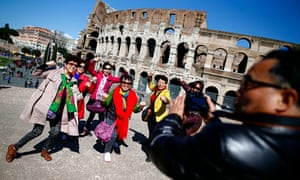 Tourists pose in front of the Colosseum in Rome