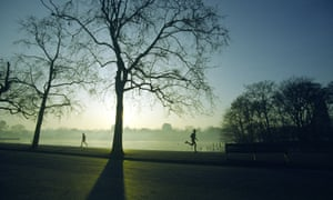 Runners at sunrise in a park by the river Thames in London.