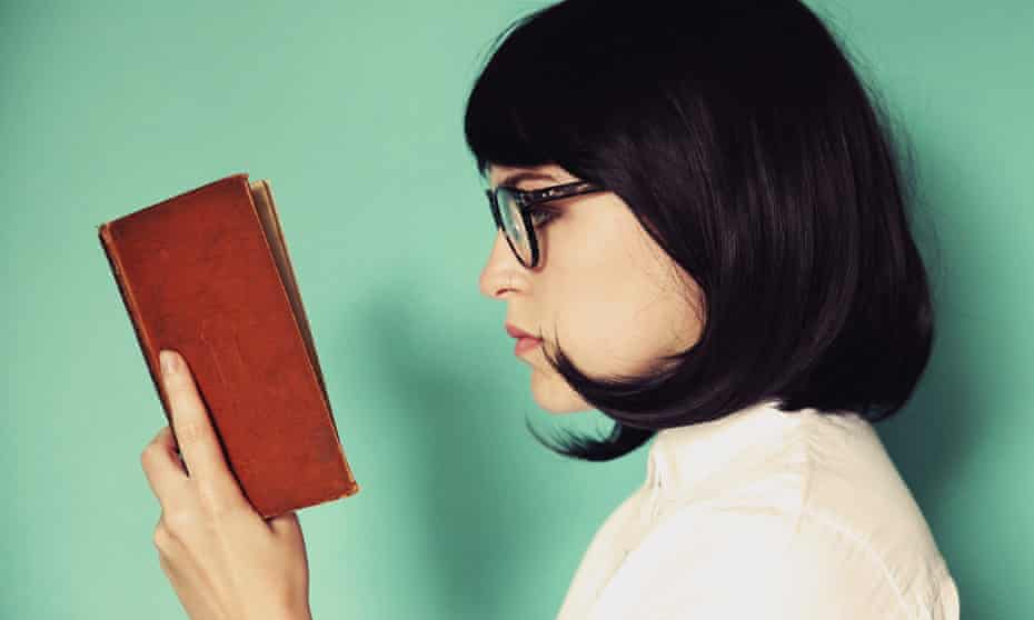 Profile of a young woman reading a book.