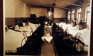 A sepia photograph; two rows of five cast-iron beds, run down the side of a hospital ward, each with a patient (they seem to be women and children). Some beds have tall wooden bedsiders, with vases and flowers.  Bare wood chairs stand at the end of each bed.