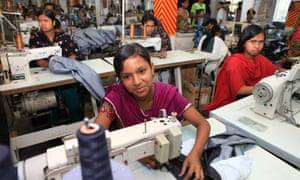 Women and girls operating sewing machines in clothes factory